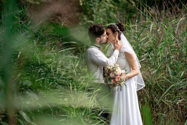 ženích a nevesta sa bozkávajú vo vysokej tráve